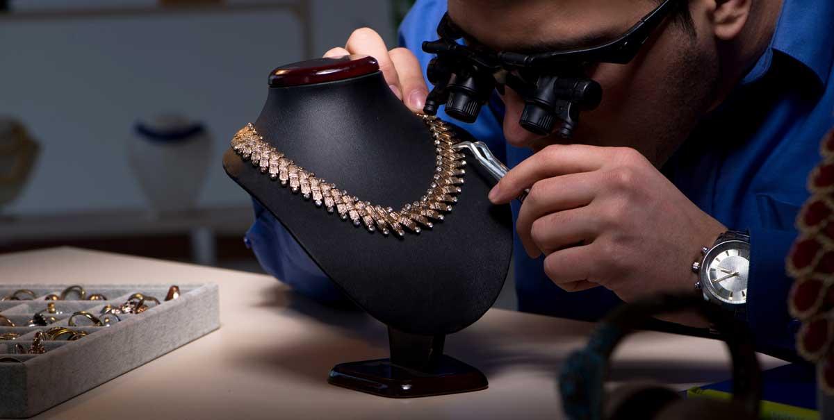 Goldschmied bei Präzisionsarbeit an Halskette