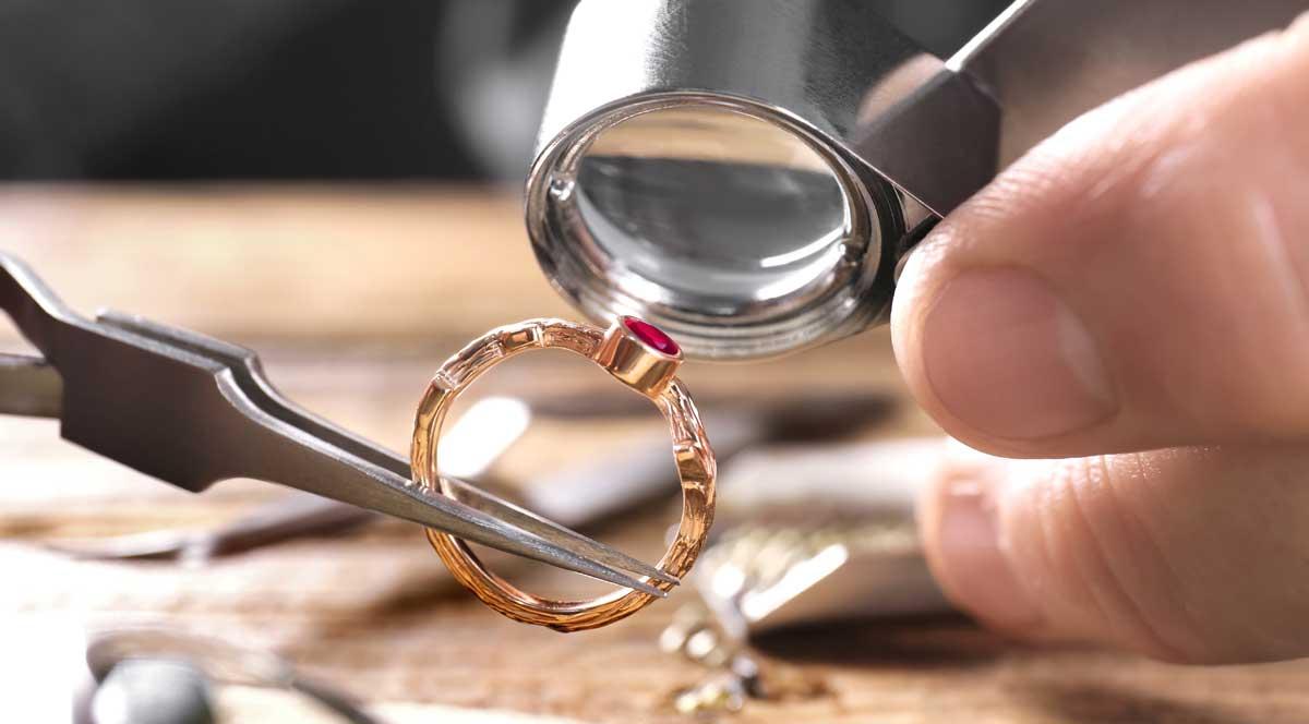 Fassung eines Brillantrings wird mit Lupe geprüft