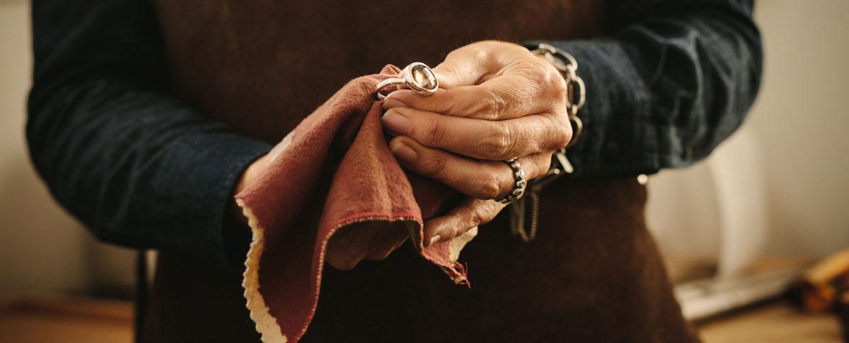 Goldschmiedin poliert Ring