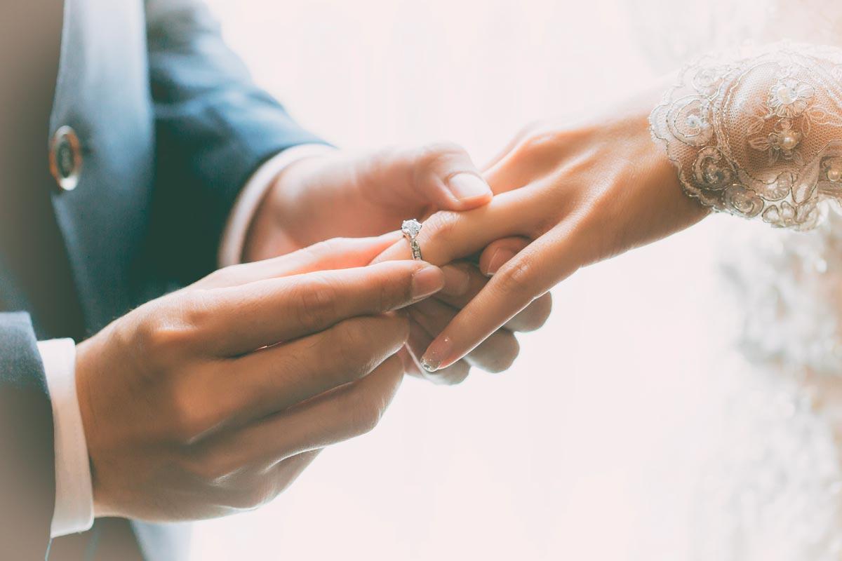 Der Bräutigam steckt der Braut den Ring an den Finger.
